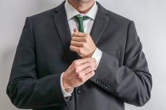 Goed geklede zakenman die zijn kokers aanpassen royalty-vrije stock fotografie