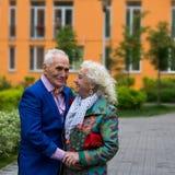 Goed-gekleed bejaard paar die in openlucht spreken Stock Afbeeldingen