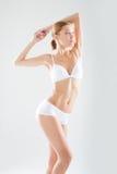 Goed gevormde gestemde jonge vrouw in het witte lingerie stellen met haar opgeheven wapens, torsomening op een manier, schoonheid Stock Foto's