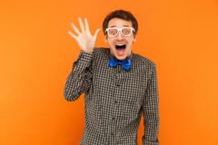 Goed hallo! Jonge volwassen gekke mens toothy glimlachende en tonende hand a stock foto's