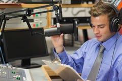 Goed het geklede geconcentreerde radiogastheer matigen zich royalty-vrije stock foto's