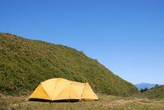 Goed wind bestand tent op het vlakke kampeerterrein. Stock Foto