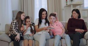 Goede atmosfeer op een grote familiegrootmoeder met haar dochter en kleinkinderen die voorbereidingen treffen beginnen op een fil stock videobeelden