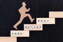Goede - beter - Beste document mens die de stappen beklimmen aan succes in een conceptueel beeld over zwarte achtergrond royalty-vrije stock foto