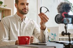 Goede keus! Knappe blogger die slim horloge op camera tonen terwijl het registreren van nieuwe video voor zijn Youtube-Kanaal stock foto's