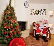 Goede Nieuwjaargeest: Kerstboom, giftzak, open haard en decoratie Kerstman en twee jonge geitjes stock foto