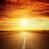 Goede rode zonsondergang en asfaltweg stock foto