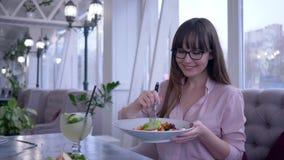 Goede voeding in koffie, portret van jonge vrouw in oogglazen met vork en plaat die ter beschikking Griekse salade en het kijken  stock video