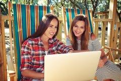 Goede vrienden die en wanneer punt bij het scherm van Com zitten glimlachen Royalty-vrije Stock Foto
