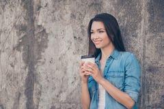 Goedemorgen! De vrolijke vrij jonge rustige donkerbruine dame heeft hete thee dichtbij concrete muur buiten, het glimlachen, drag stock afbeeldingen