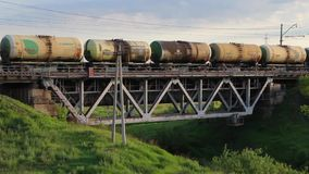 Goederentrein met de auto's die van de aardolietank over de spoorwegbrug overgaan stock video