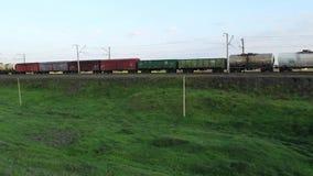 Goederentrein met ladingswagens en tank die door gebieden in platteland overgaan stock videobeelden