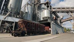 Goederentrein met landbouwgewassen als ladingsvervoer die zich bij grote korrelterminal dichtbij overzees bewegen Leegmakende kor stock videobeelden