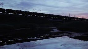 Goederentreinpassen over de Spoorwegbrug, Silhouet van Trein die Brug kruisen stock footage