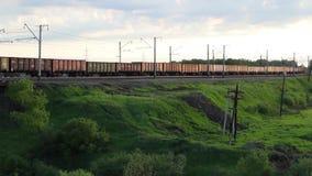 Goederentreinvervoer die een Spoorwegspoor doorgeven bij Zonsondergang stock video