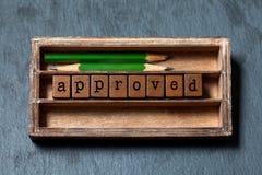 Goedgekeurd en toegelaten symbolisch concept Uitstekend vakje, houten kubussen met oude stijlbrieven, groene potloden Grijze stee stock fotografie