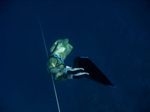 Goes down by the line. Freediver makes deep dive by line near the coral reef in Blue Hole, Dahab, Egypt royalty free stock photo
