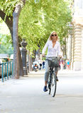 She goes everywhere by bike. Full length shot of a young woman in the street with a bicycle Stock Photos