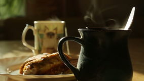 Goes the steam from hot tea, two cups. Goes the steam from hot tea on a background of empanadas stock video footage