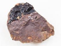 Goethite aggregates on limonite stone on white. Macro shooting of natural mineral rock specimen - concretion of goethite aggregates on limonite stone on white Royalty Free Stock Photography