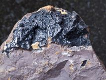 Goethite ore on limonite stone close up. Macro shooting of natural mineral rock specimen - goethite ore on limonite stone on dark granite background from Royalty Free Stock Photo