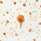 Gofra rożek z pomarańczowymi jaskierów kwiatami Wiosna lub lato nastroju pojęcie zdjęcie stock