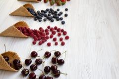 Gofra słodki lody konusuje z malinkami, wiśniami, truskawkami i czarnymi jagodami nad białym drewnianym tłem, boczny widok fotografia royalty free