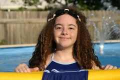 Goggle Girl. A young girl swimming in a pool, with goggles on her head, and dripping from just emerging from the water stock photography