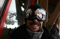 Goggle Man Smile. Middle-aged gut with goggles and a cheesy grin. Seems real happy to be at the ski resort. In the reflection, a person can be seen smiling at Royalty Free Stock Images