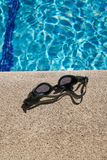 Goggles on curb of swimming pool Stock Photos