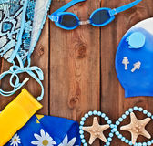 Goggles, shells, swimsuit on a wooden background. Royalty Free Stock Photography