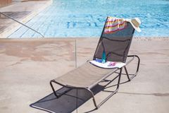 Lounge chair by a swimming pool with sunscreen and a towel Stock Image