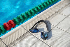 Goggles for swimming on a pool side Royalty Free Stock Images