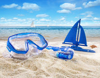 Goggles and toy sailboat in sand Royalty Free Stock Photography