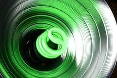 Goin' Green. Green compact fluorescent bulb lights up in a reflector royalty free stock photography