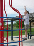 Going For it. Little boy climbing to the top of a Jungle Gym Royalty Free Stock Image