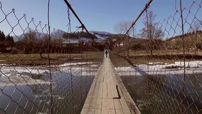 Going across the bridge. Person walking on a wooden suspension bridge across the river. Beautiful winter landscape. Mountains. Floating of ice. Efect shaking stock footage