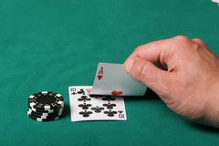 Going all in. Cards in a black jack game, player checking his hand Stock Images