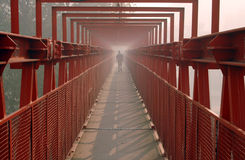 Going away. Man walking by a red iron bridge. industrial style. Covered in thick smog caused by forest fire in Buenos Aires Argentina Stock Image