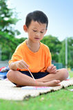 Going back to school : Boy drawing and painting over green grass Stock Images