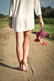 Going barefoot. Figure of a girl walking barefoot in the sand Royalty Free Stock Images