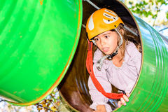 Going through the barrels. Little girl is going through the barrels in adventure park royalty free stock photos