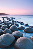 Going Bowling. Bowling Ball beach just south of Point Arena, Ca is home to dozens of six ft perfectly round boulders.  Sunrise casts a soft pastel color onto the Stock Photos