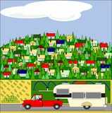 Going Camping. A gentleman is going camping with his truck and a travel trailer. The hill is full of houses and trees and a field has hay bales and a irrigation Stock Images