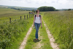 Going for country walk. A woman walk down a farms lane in summer Royalty Free Stock Photography