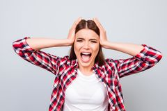 Going crazy and insane, psycho and agression. Close up portrait. Of shouting stressed young lady on pure light background, wearing casual clothes, screaming Royalty Free Stock Images