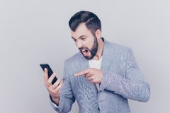 Going crazy and insane, psycho and agression. Close up portrait. Of shouting stressed young brunet bearded entrepreneur, pointing at his phone, on pure light Stock Photos