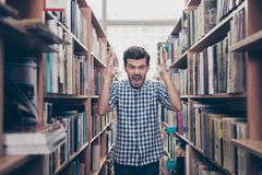 Going crazy and insane, psycho and agression. Shouting stressed. Young brunet bearded student is blasting standing between the book shelves in the library royalty free stock images