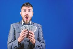 Going crazy. Making money with his own business. Currency broker with bundle of money. Bearded man holding cash money royalty free stock photography