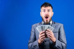 Going crazy. Making money with his own business. Currency broker with bundle of money. Bearded man holding cash money. Rich businessman with us dollars royalty free stock images
